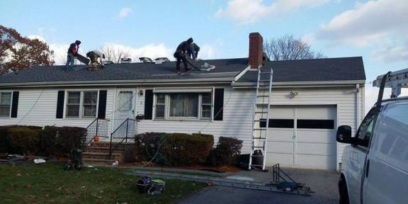 Workers repairing shingles on roof